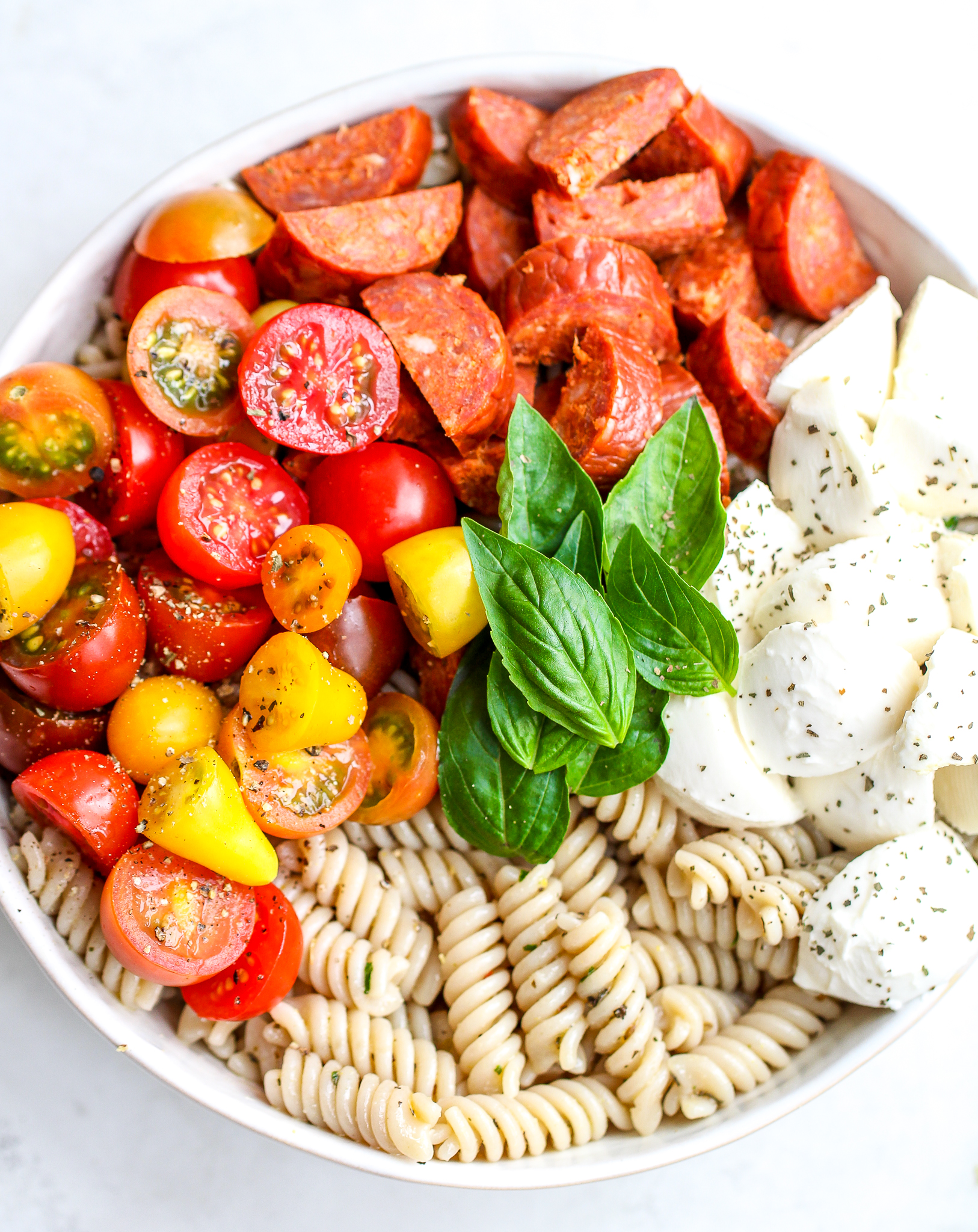 Ingredients for Italian pasta salad arranged in a white serving bowl - cooked gluten free pasta,