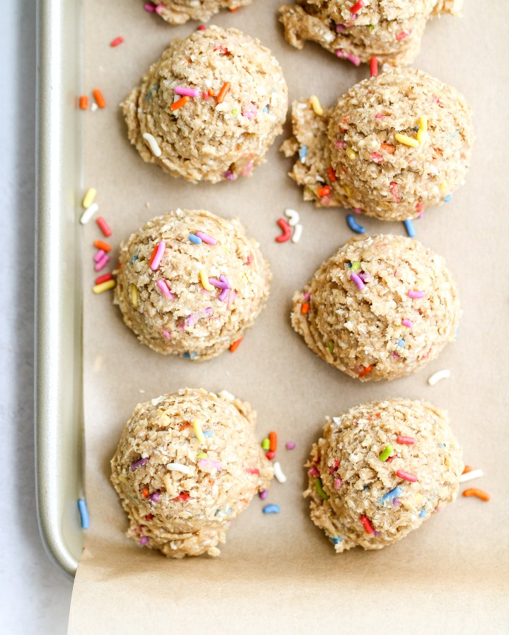 scoops of cake batter protein bites on a parchment lined baking sheet