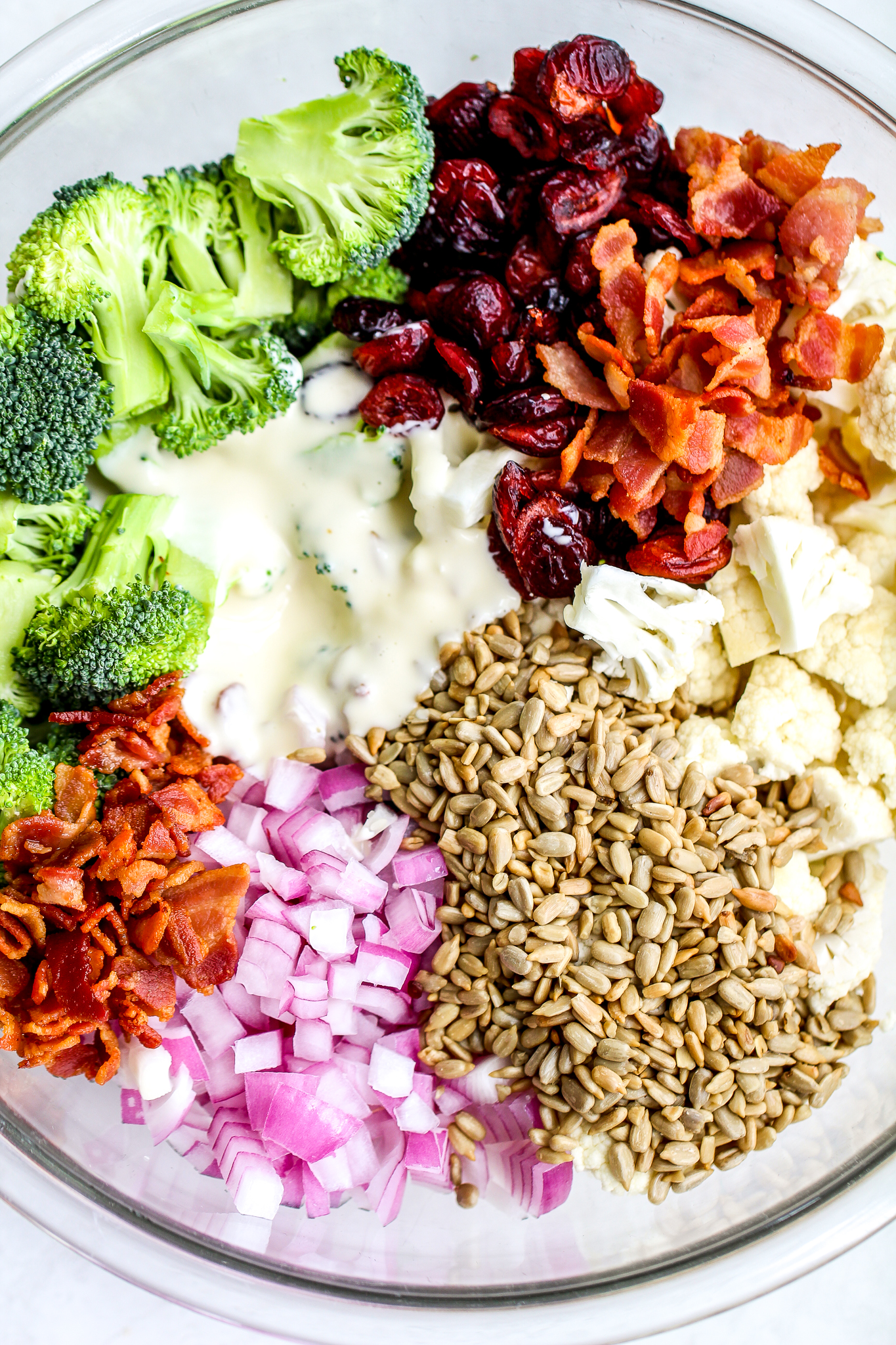 ingredients for broccoli cauliflower salad separated in a large glass mixing bowl. There are broccoli and cauliflower florets, dried cranberries, chopped bacon, diced red onion, sunflower seeds and creamy dressing
