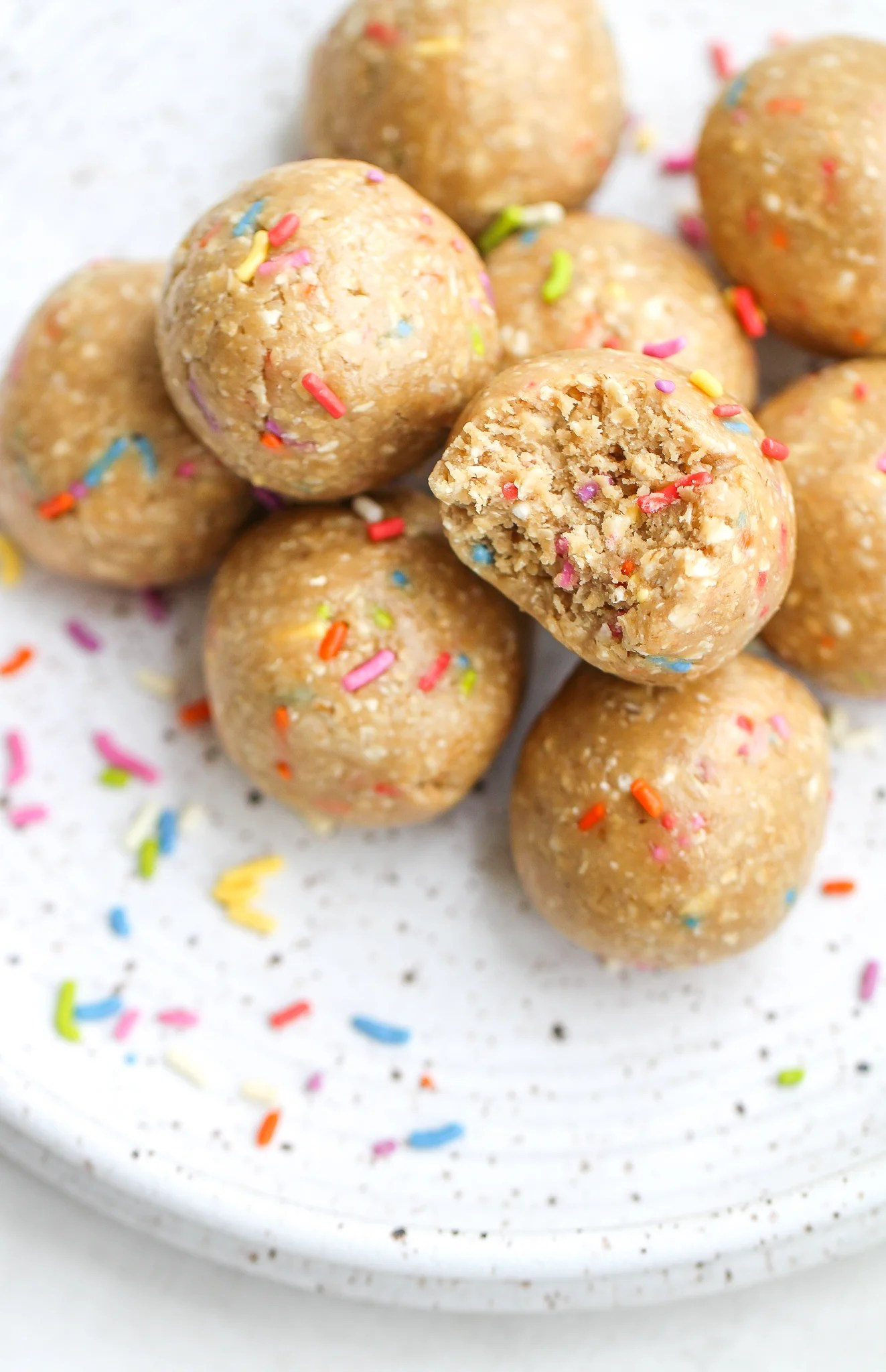 cake batter protein bites stacked on a speckled ceramic plate. One has a bite taken out of it and there are sprinkles scattered on the plate