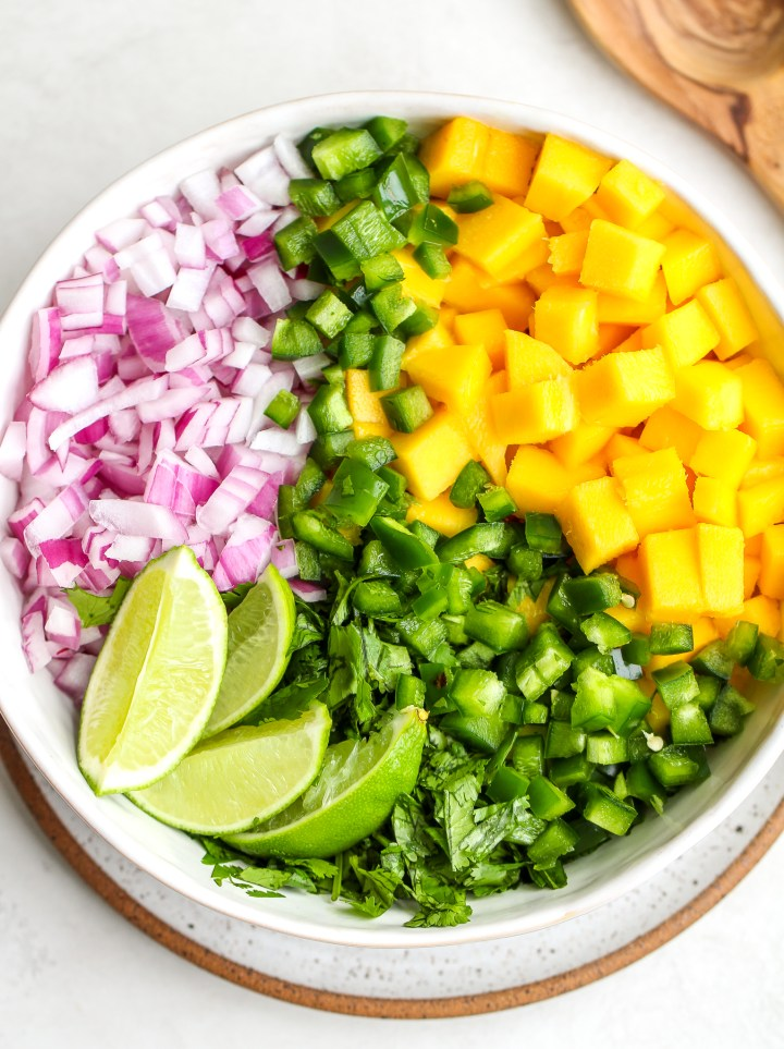 ingredients separated for mango salsa in a white serving bowl