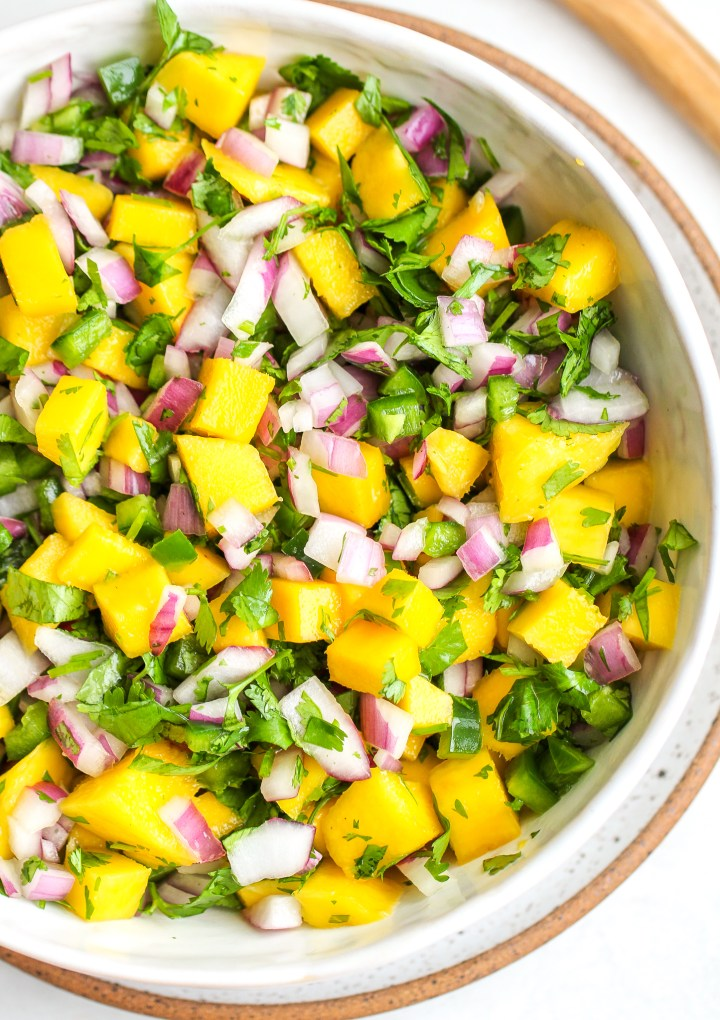 fresh mango salsa in a white serving bowl - there is bright yellow cubed mango, diced green jalapeño, chopped cilantro and diced red onion