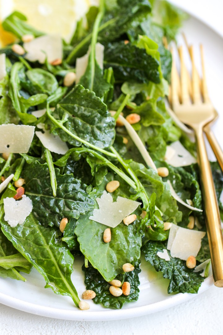 lemony kale and arugula salad on a white plate with gold forks on the side - the salad is topped with shaved parmesan cheese and toasted pine nuts