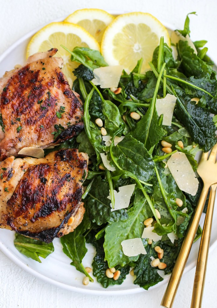 kale and arugula salad on a white plate with a side of grilled chicken thighs and lemon slices