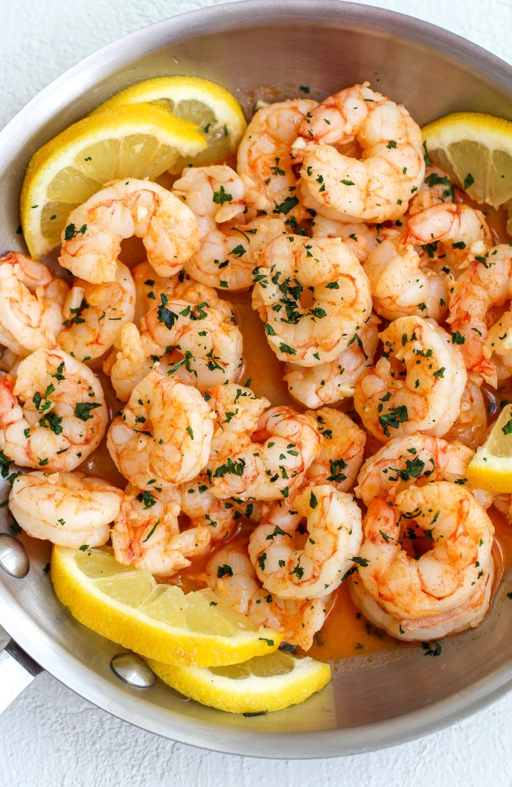 lemon garlic shrimp in a small stainless steel pan with sliced lemons on the side and fresh chopped parsley on top