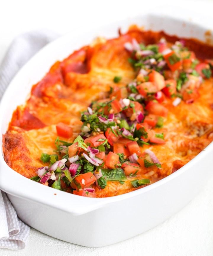 healthy enchiladas in a white baking dish topped with fresh pico de Gallo