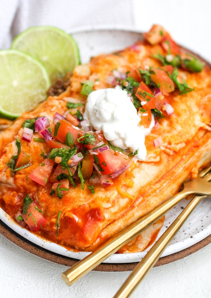 healthy enchiladas on a white speckled ceramic plate with pico de Gallo and sour cream on top. there are lime slices and gold forks on the side