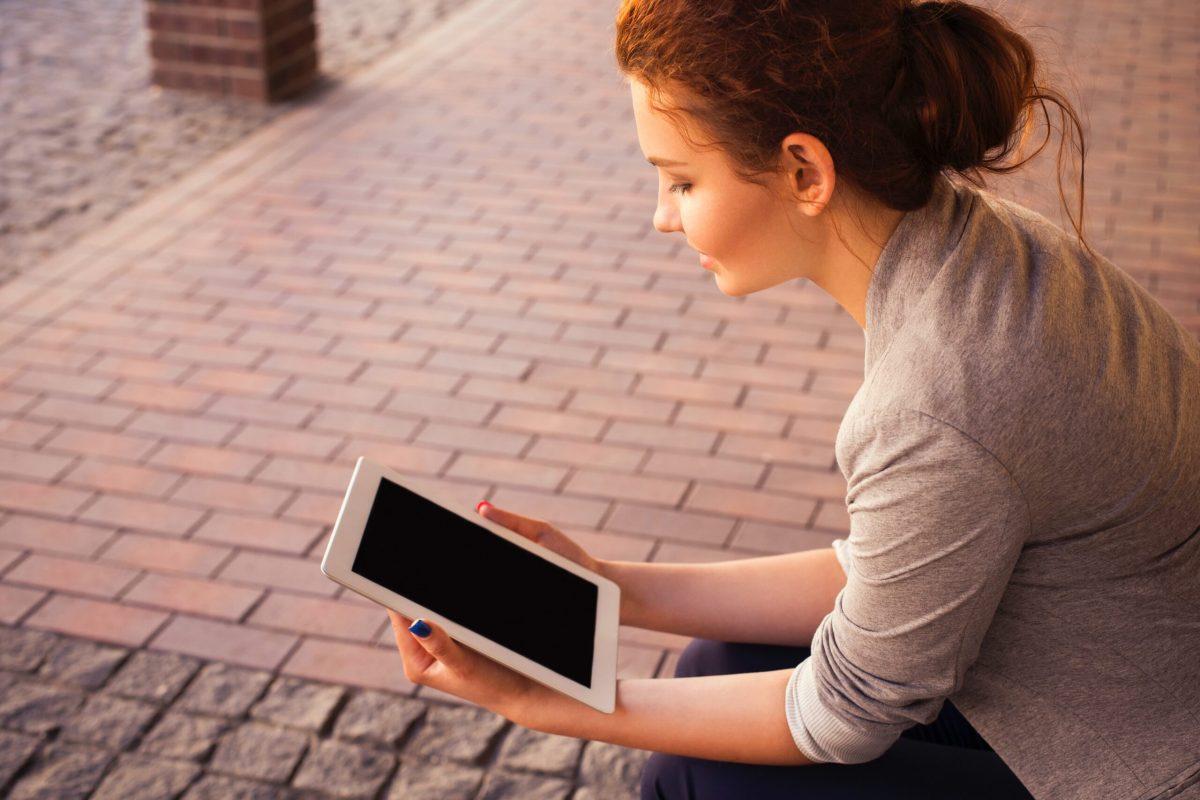 woman holding white iPad