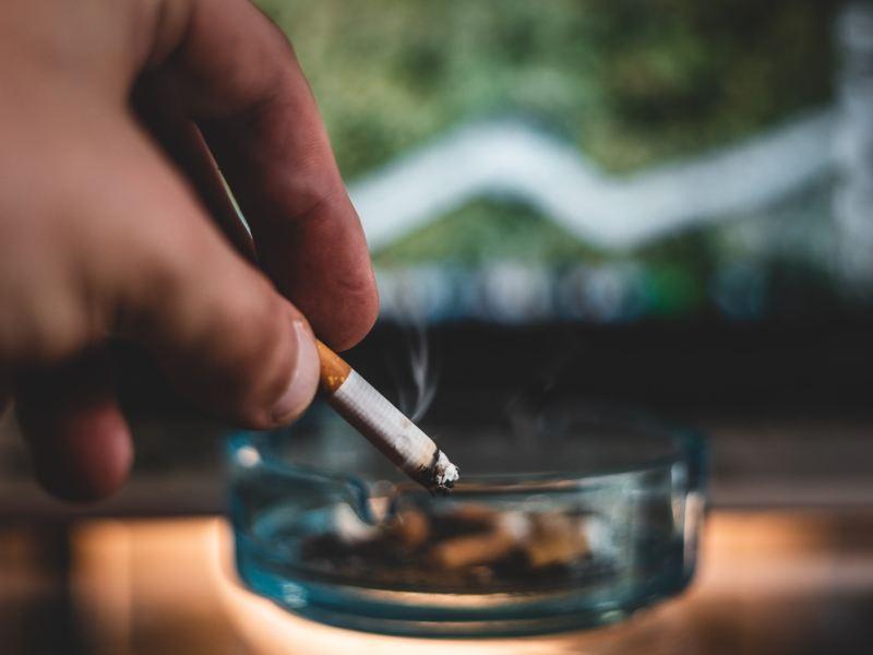person holding cigarette stick and round glass ashtray