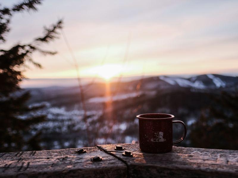black ceramic mug on brown wooden table during sunset