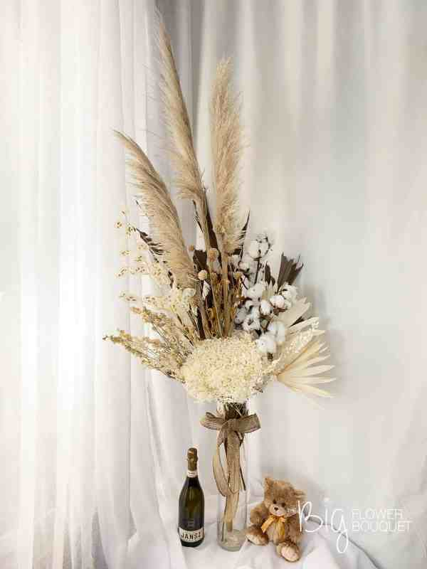 Everlasting Nature Deluxe Size Dry Flower Arrangement in Tall Glass Vase with Jansz Sparkling Wine and Teddy Bear as a size comparison by The Big Flower Bouquet