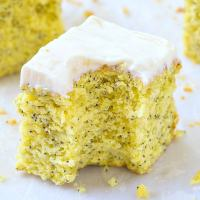 A slice of flourless lemon poppy seed breakfast cake topped with a protein-packed frosting