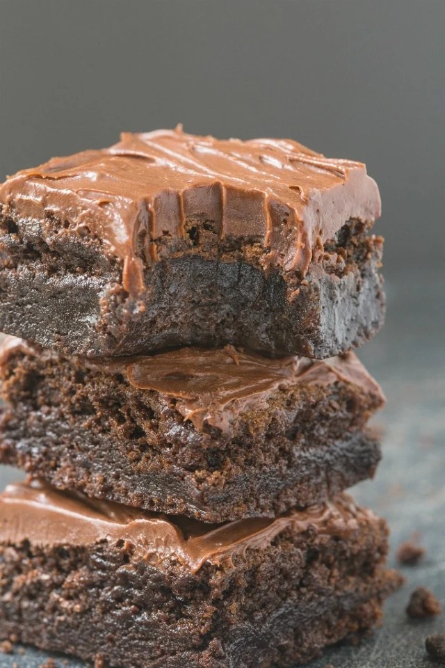 A close up shot of flourless fudge brownies with a healthy, thick frosting