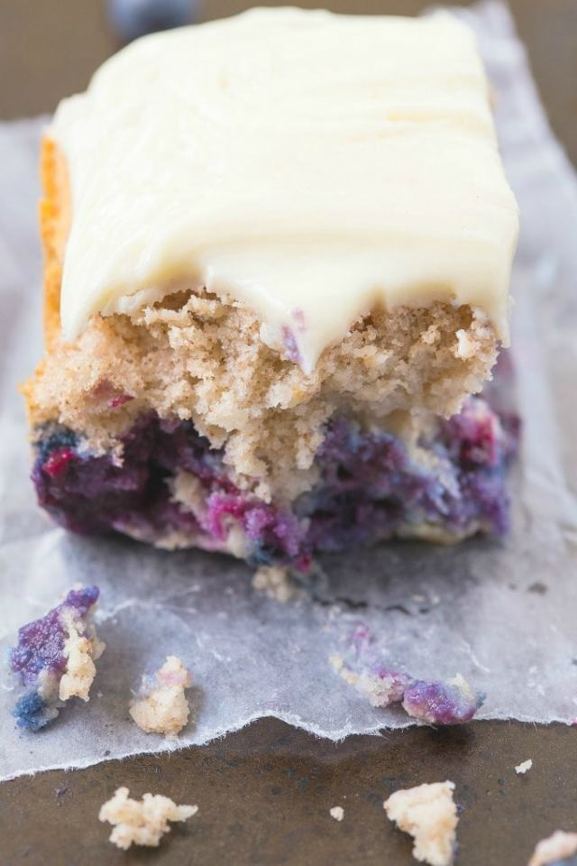 A piece of healthy flourless blueberry breakfast cake with an interior shot bursting with blueberries and topped with a vanilla cream frosting