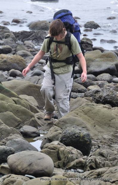 Daniel hiking a boulder-strewn section of beach.