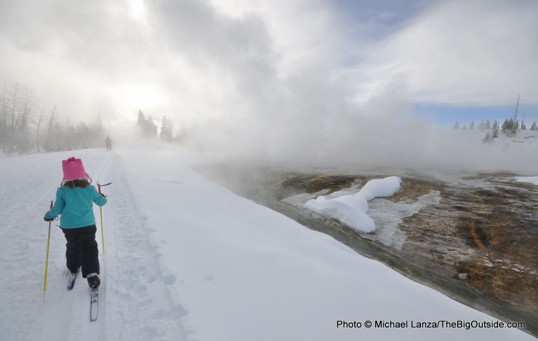 A young girl cross-country skiing the Biscuit Basin Trail through the Upper Geyser Basin in Yellowstone National Park.