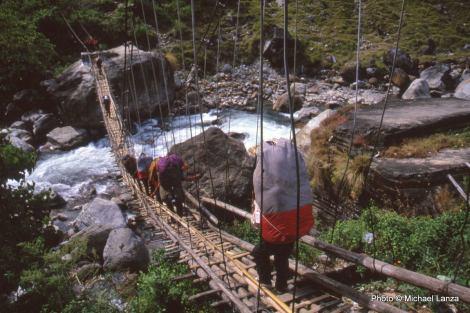 Porters cross a suspension bridge, Marsyangdi River, Annapurna Circuit.