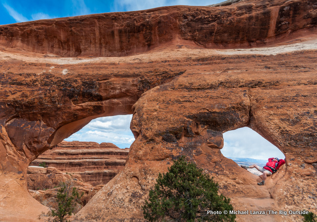 Jeff Wilhelm reclines in Partition Arch, Arches National Park.
