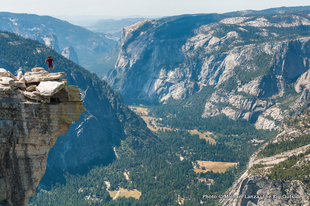 A hiker standing on The Visor on the summit of Half Dome in Yosemite.
