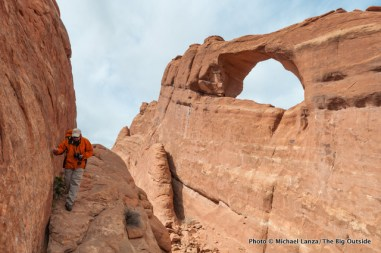 A hiker below Skyline Arch in Arches National Park.