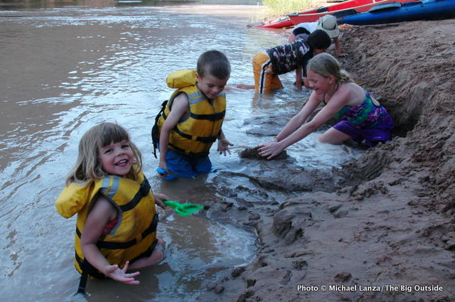 Children playing in riverbank mud at a campsite on the Colorado River, Canyonlands National Park.