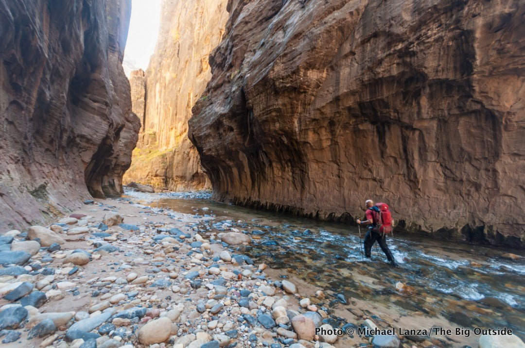 A backpacker on day two in The Narrows of Zion National Park.