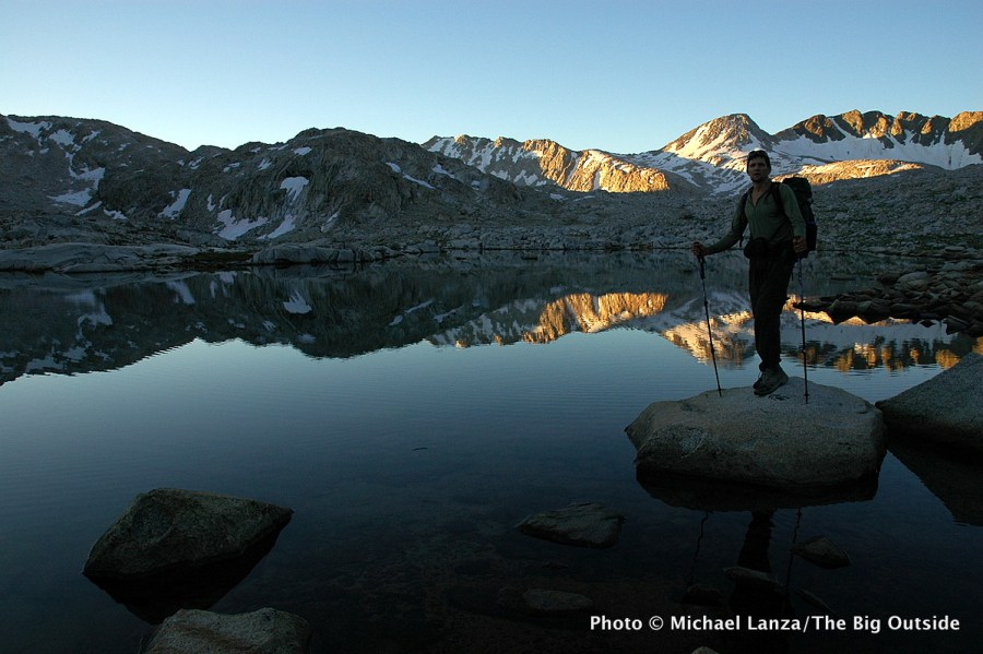 A backpacker at Sapphire Lake on the John Muir Trail in Evolution Basin, Kings Canyon National Park.