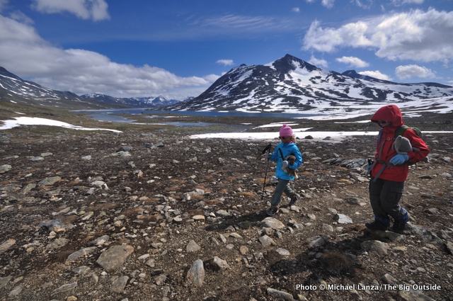 A young boy and girl trekking up the Langvatnet valley in Norway's Jotunheimen National Park.