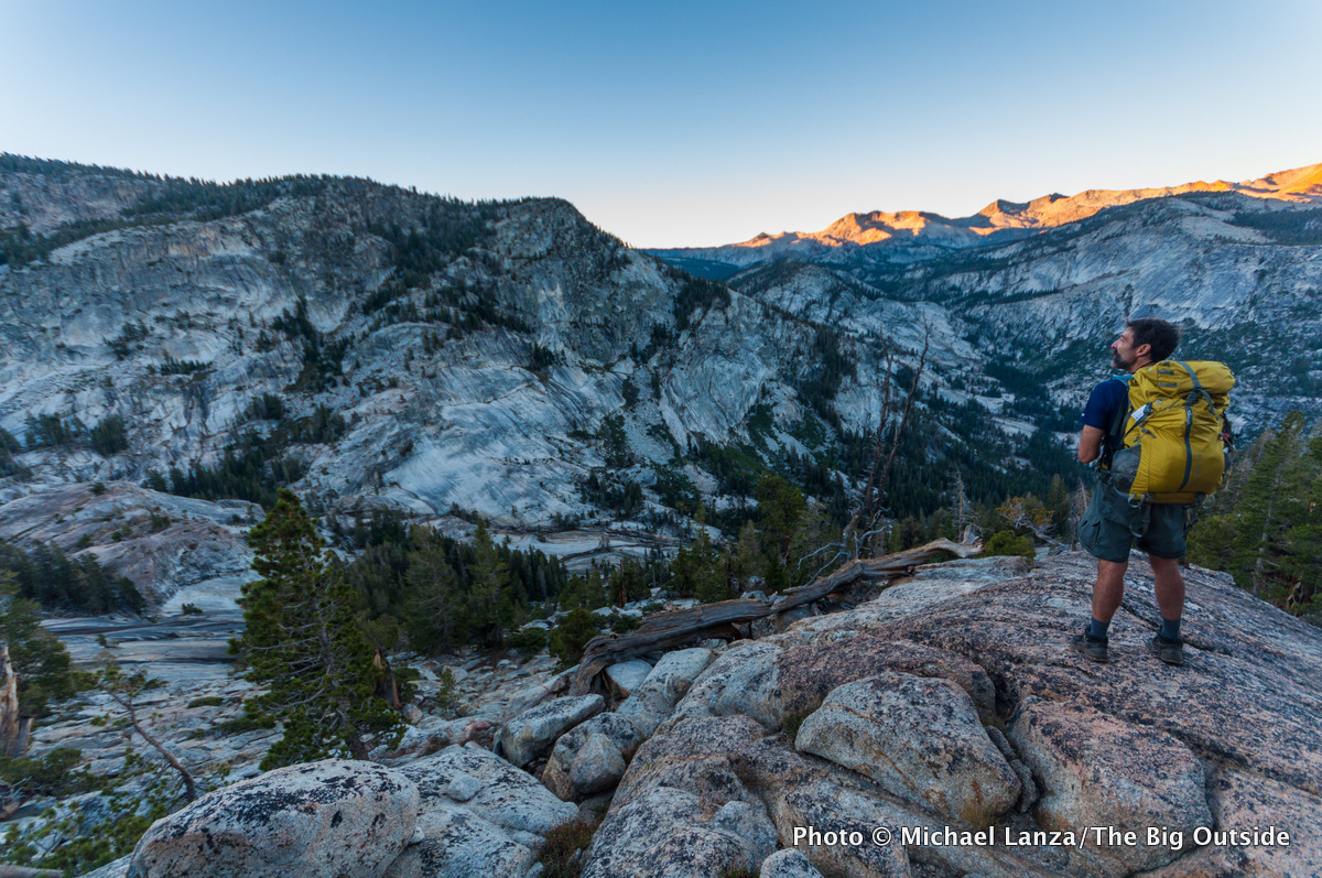A backpacker hiking at dawn above the Lyell Fork of the Merced River, Yosemite National Park.