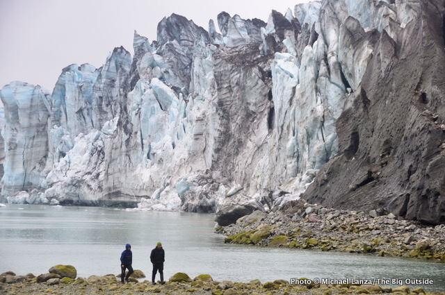 Kayakers hiking below the Lamplugh Glacier, Glacier Bay, Alaska.
