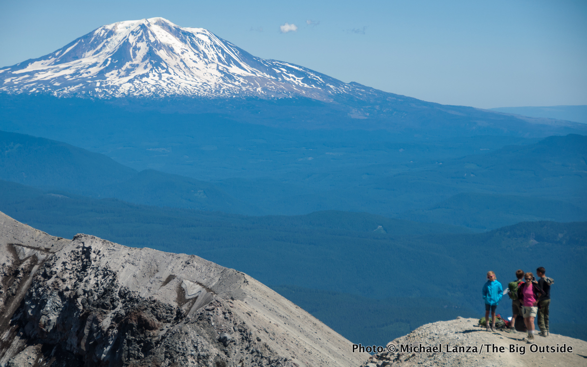 Hikers on the crater rim of Mount St. Helens, with Mount Adams in the distance.