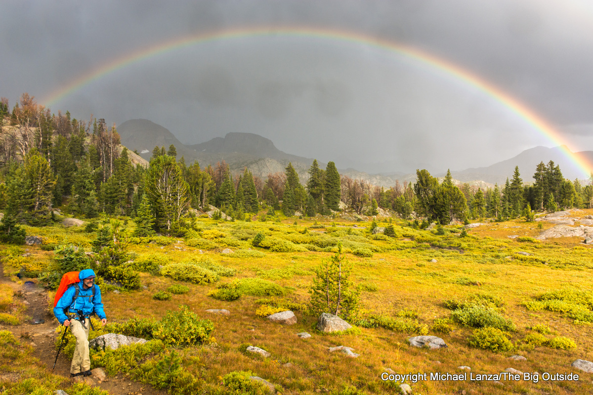 A backpacker hiking below a rainbow in Wyoming's Wind River Range.