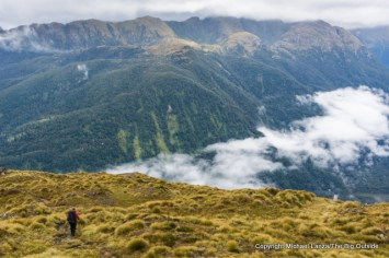A hiker on the Dusky Track in the Pleasant Range, Fiordland National Park, New Zealand.