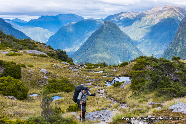 A trekker climbing to Centre Pass on the Dusky Track, Fiordland National Park, New Zealand.