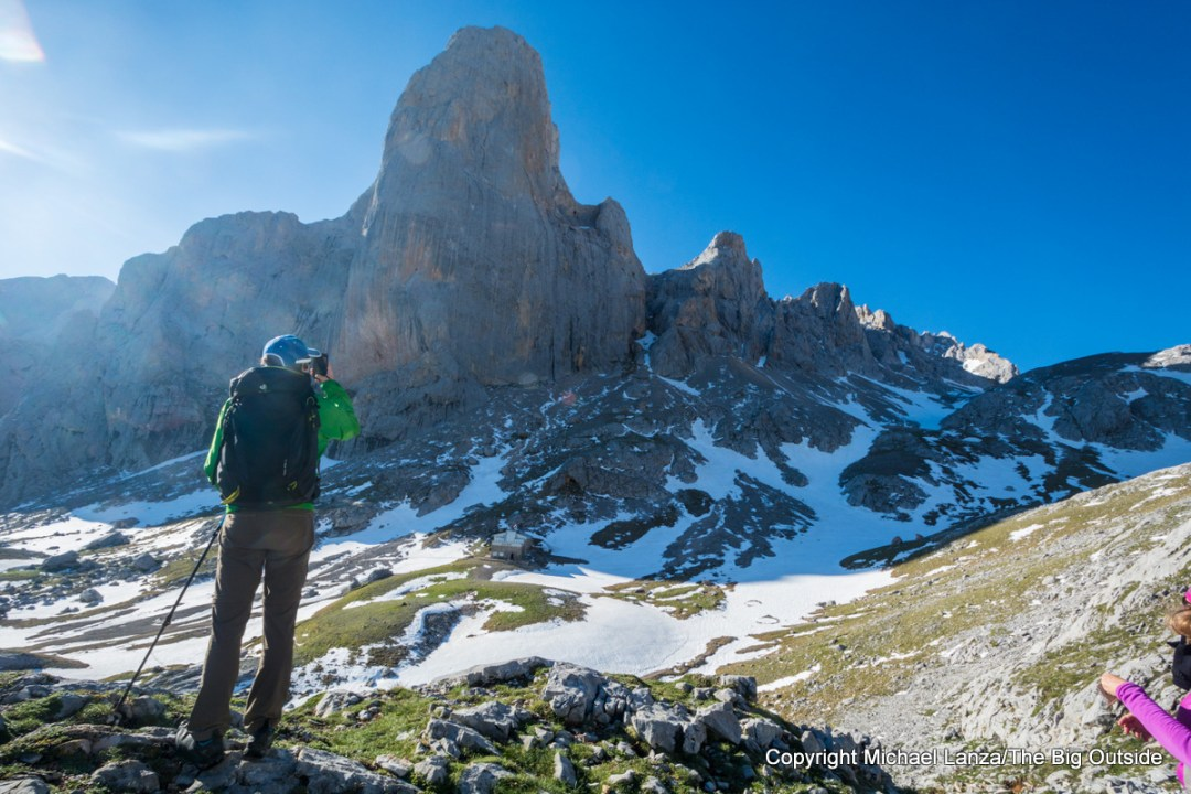 A hiker overlooking the Naranjo de Bulnes peak in Spain's Picos de Europa Mountains.