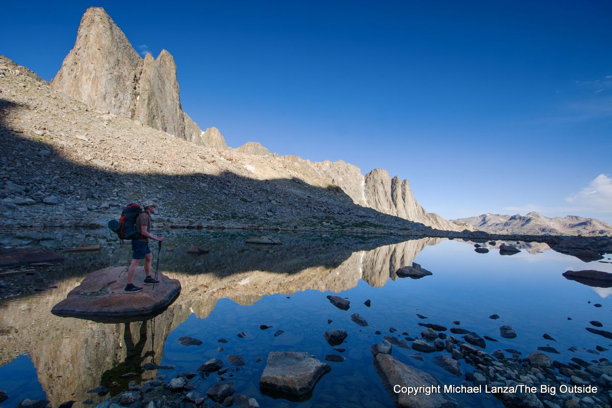 A backpacker at a small tarn in the upper valley of Middle Fork Lake on the Wind River High Route, Wyoming.