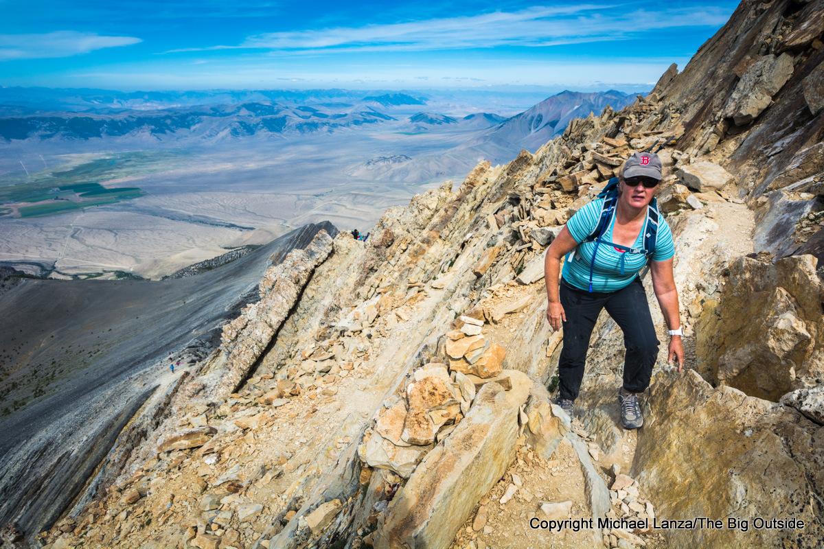 A hiker scrambling Chickenout Ridge on Idaho's 12,662-foot Borah Peak.