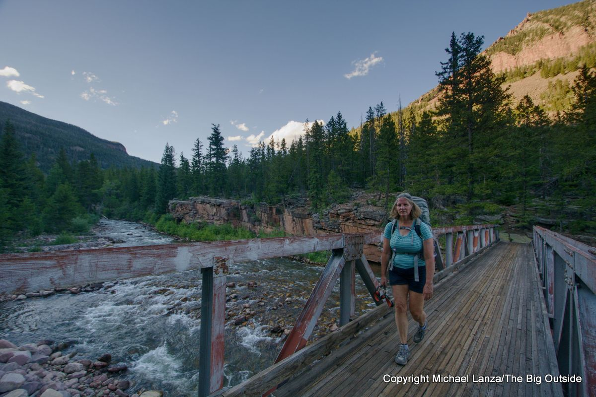 A backpacker crossing the bridge over the Uinta River on the Chain Lakes Atwood Trail 43, High Uintas Wilderness, Utah.