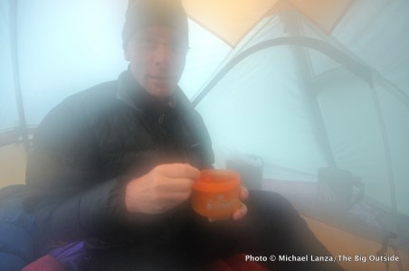 A backpacker inside a damp tent on a rainy evening in the mountains of Olympic National Park.