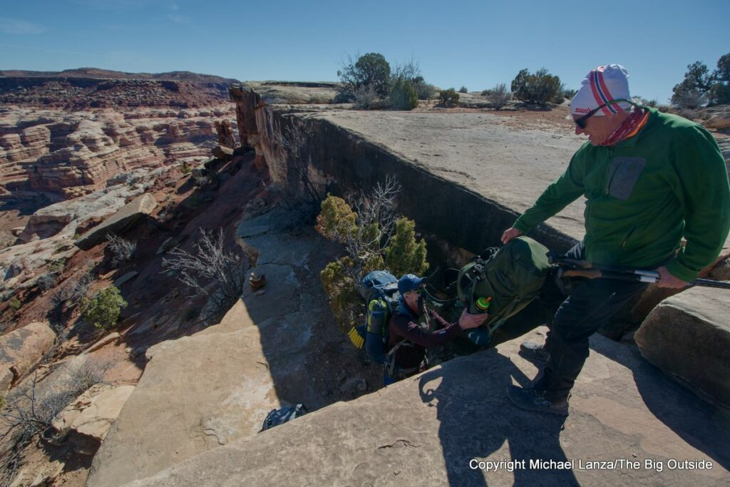 Backpackers passing packs on the trail off Maze Overlook in the Maze District, Canyonlands National Park.