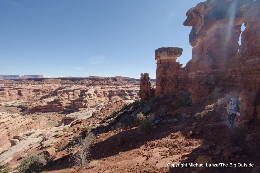A backpacker on the trail off Maze Overlook in the Maze District, Canyonlands National Park.