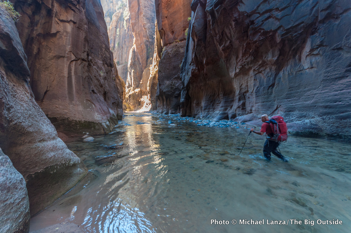 A backpacker in The Narrows of Zion National Park.