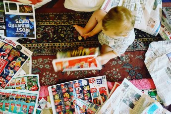 baby playing with newspapers