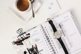 desk with notebook, watch and coffee