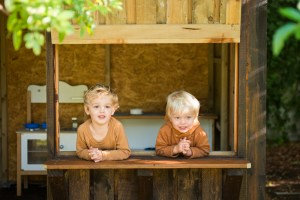 Two toddlers looking out of treehouse hatch