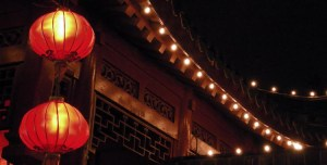 Two red lanterns hanging next to a pagoda style building at night