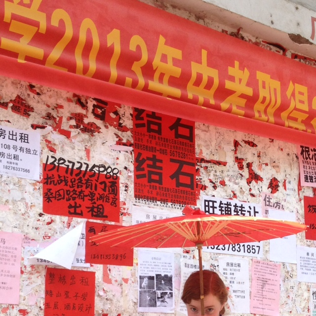 Wall with tattered red and white posters pasted on. Nell holds a red parasol, standing in front of the wall
