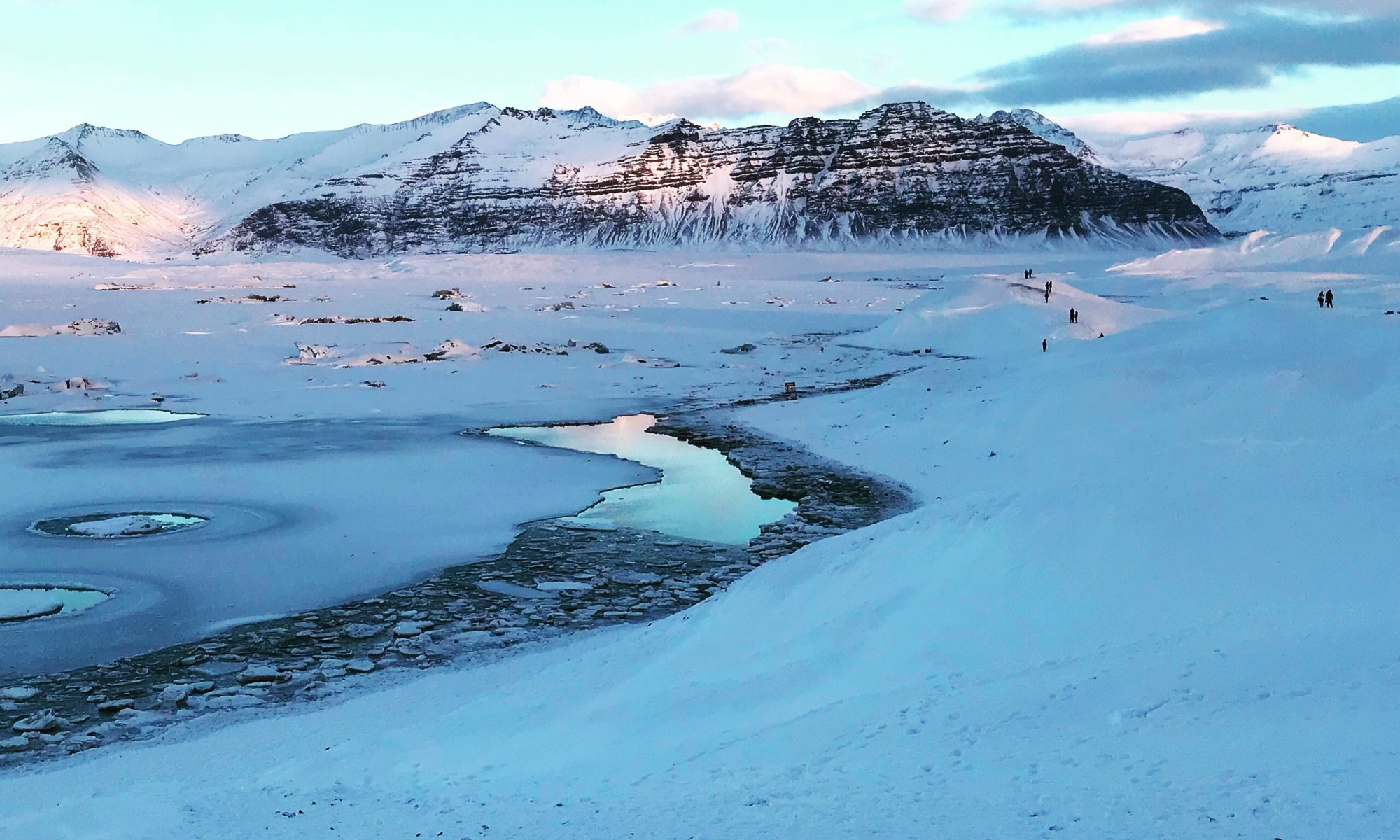 Photo of a river through ice winding its way towards a snowy mountain