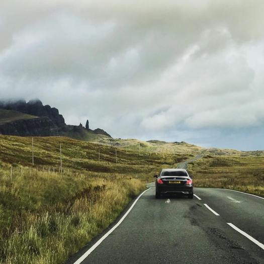 Photo of a car driving towards the Oldman of Storr