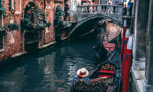 Photo of a gondola moored by a bridge in Venice